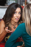 Serious Conversation in Cafe. Serious women gesturing with hands in conversation in restaurant Royalty Free Stock Photo