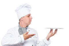 Serious cook shows his hand on the empty tray on a white Stock Image
