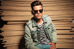 Serious cool casual man wearing sunglasses and sits stock images