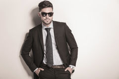 Serious and cool sexy business man wearing sunglasses. And standing with hands in his pockets Royalty Free Stock Photos