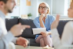 Serious counselor. Serious mature blonde female listening attentively to young couple argument while sitting in front of them royalty free stock image