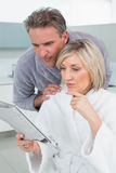 Serious couple in bathrobes reading newspaper Royalty Free Stock Photography