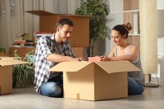 Serious couple boxing belongings on the floor moving house stock photo