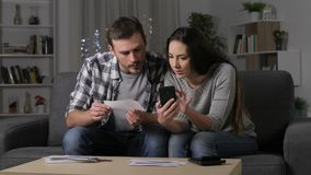 Couple checking receipts on phone at home. Serious couple checking receipts on smart phone in the night at home stock video