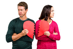 Serious couple holding cracked heart shape Royalty Free Stock Photos