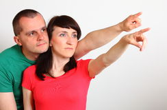 Serious couple looking and pointing into distance. Serious women and men looking and pointing into distance, married pointing with finger at something or someone Royalty Free Stock Images