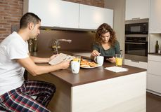 Serious couple reading news in a home breakfast Stock Photos