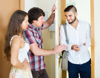 Serious couple and salesman talking. Serious couple and happy young salesman talking near the entrance royalty free stock image