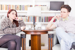 Serious couple sitting on armchairs in the library Stock Photos