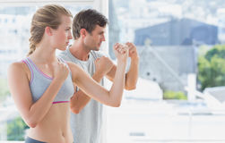 Serious couple standing in boxing stance in fitness studio Stock Images