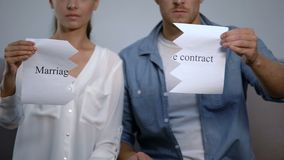 Serious couple tearing into pieces marriage contract phrase on cardboard. Stock footage stock video footage