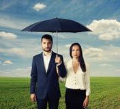 Serious couple under umbrella Stock Images