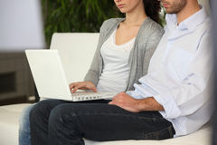 Serious couple using a laptop stock images