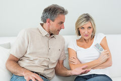 Serious couple watching tv at home Stock Photos