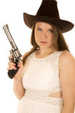 Serious cowgirl holding a pistol wearing a white dress Stock Photo