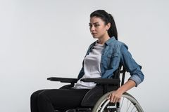 Serious crippled woman using wheelchair. Serious problem. Beautiful nice crippled woman posing on the isolated background while sitting in the wheelchair and Royalty Free Stock Photos