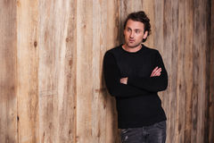 Serious curly man in black sweater standing with arms crossed Stock Photo