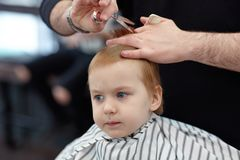 Serious cute blond baby boy with blue eyes in a barber shop having haircut by hairdresser. Hands of stylist with tools scissor, b royalty free stock photography