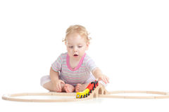 Serious cute child is playing with train stock photos