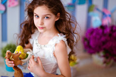 Serious cute curly haired young girl in a blue skirt, close up Royalty Free Stock Image