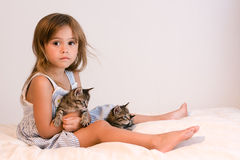 Serious, cute girl holding tabby kittens on soft off-white comforter. Cute little four year old girl holding two tabby kittens while sitting on a soft, off-white Stock Image