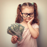 Serious cute kid in glasses looking on dollars in hand and think Royalty Free Stock Image