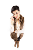 Serious cute young woman on the phone looking at camera Royalty Free Stock Images
