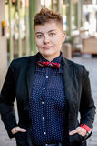 Serious Dapper Gender Fluid Young Woman. Serious dapper young gender fluid woman on city sidewalk Royalty Free Stock Photos