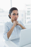 Serious dark haired woman looking at camera sitting at her desk Stock Photos
