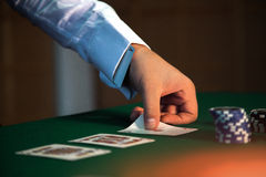 Serious dealer puts the last card on the table Royalty Free Stock Photography