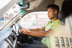 Serious delivery man driving his van Stock Photo