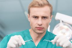Serious dentist holding dental pick Stock Photography