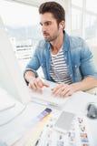 Serious designer enjoying music and typing on keyboard Royalty Free Stock Photo