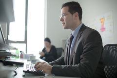 Serious devoted business man work in office on computer. Real economist business people, not models. Bank employees discussing. Serious devoted business man work Royalty Free Stock Photography