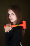 Serious Do-It-Yourself. Young handywoman carrying a mallet on her shoulder Stock Image