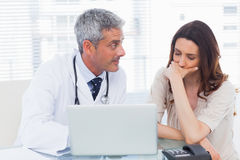 Serious docter showing something on laptop to his patient Stock Image