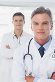 Serious doctor with arms crossed standing Stock Photography