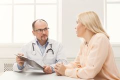 Doctor consulting woman in hospital. Serious doctor consulting women and showing her test results, healthcare and medical concept, copy space Royalty Free Stock Photography