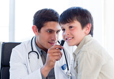 Serious doctor examining little boy's ears. At the practice stock images