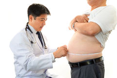 Serious doctor examining a patient obesity royalty free stock photography