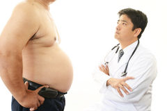 Serious doctor examining a patient obesity Royalty Free Stock Photo