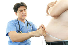 Serious doctor examining a patient obesity Royalty Free Stock Images