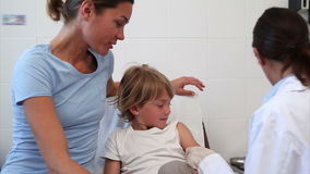 Serious doctor giving child an injection Royalty Free Stock Images