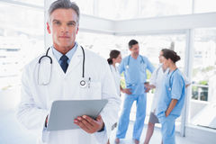 Serious doctor holding clipboard. In front of his medical team Stock Images