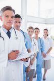 Serious doctor holding clipboard and standing in front of his me. Dical team in row Stock Photo