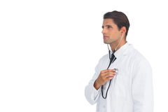 Serious doctor holding up stethoscope to his chest Stock Photo