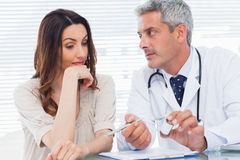 Serious doctor listening to his patient Royalty Free Stock Image