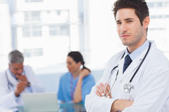 Serious doctor looking at camera with colleagues behind Royalty Free Stock Photography