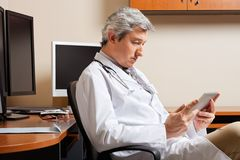 Serious Doctor Looking At Digital Tablet Stock Photography