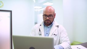 Serious doctor looking at a laptop in a bright office. 4 k. healthcare, medical and technology concept. Male doctor with laptop pc writing prescription stock video